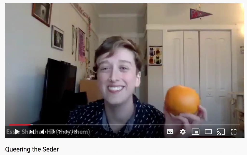 a screenshot of a paused YouTube video which shows a person in a patterned shirt holding an orange