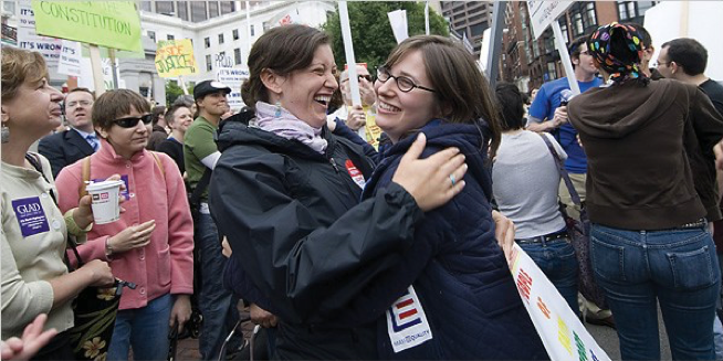 Image of Leah Krieger and Orly Jacobovits celebrating outside the Massachusetts State House with a crowd of people.