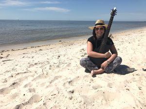 Rabbi Alexis Pinsky sitting on the beach, holding a guitar.