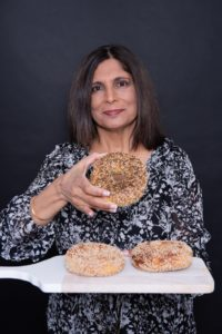 Shulie Madnick holding up a bagel