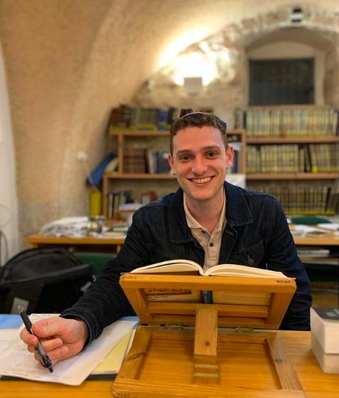 Bennett Decker sitting at a desk with an open book